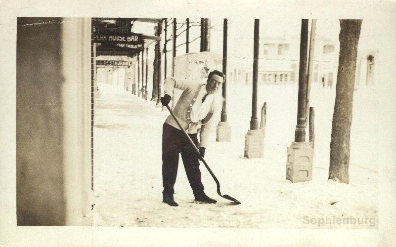 Man shoveling snow off sidewalk in front of Seekatz Opera House, 1915. (0001-07PC)