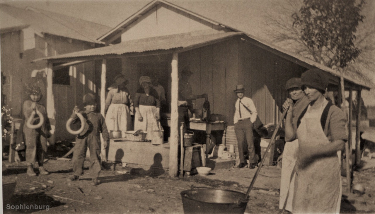 Family butchering in 1926. Notice the size of the sausage links and the women rendering the hog fat to make lye soap.