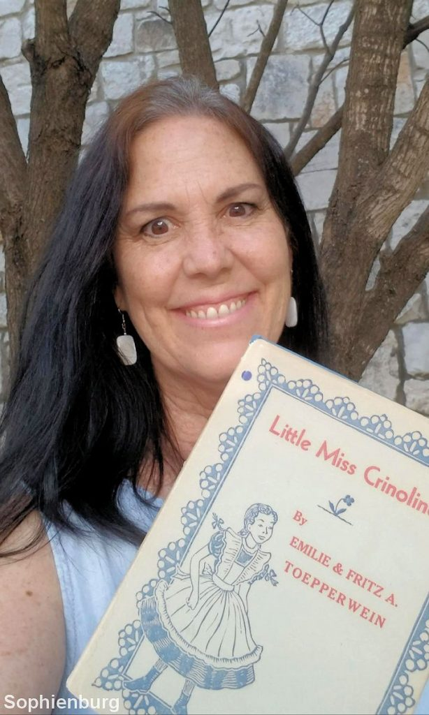 "Keva Hoffmann Boardman shows off her copy of ""Little Miss Crinoline"" by Fritz and Emilie Toepperwein."