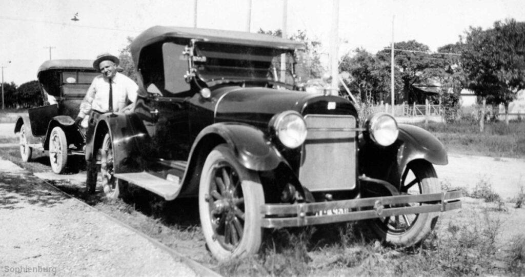 Alwin Carl Moeller standing beside his automobiles.